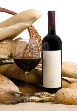 A glass of wine and assorted breads. The wine bottle has a blank lable that can be filled in.