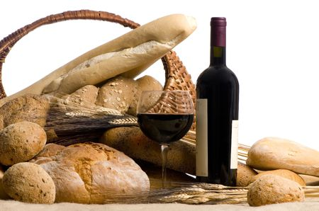 A glass of red wine with and assortment of breads on a white background photo