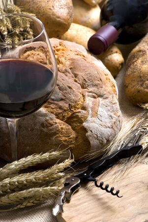 Red wine with an assortment of fresh breads. photo