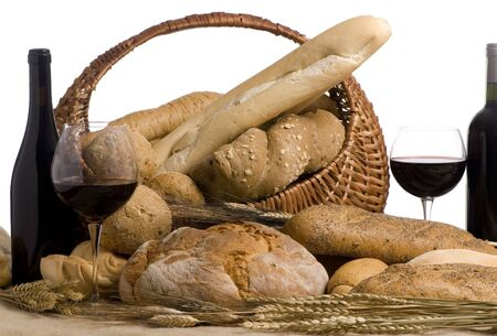 Two bottles of red wine and an assortment of fresh breads photo