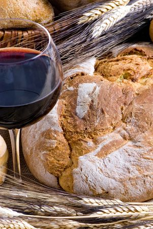 An inviting glass of red wine with an assortment of fresh breads photo