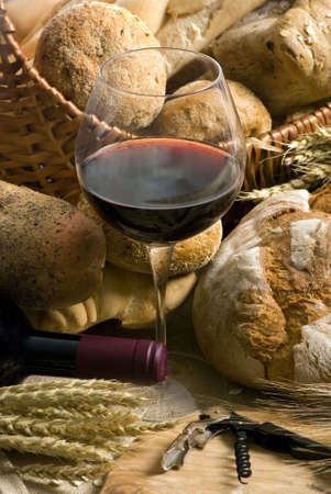An inviting glass of red wine along with an assortment of fresh breads Stock Photo