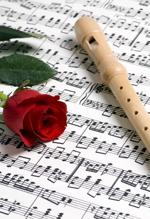 A complicated musical piece with a single rose and a flute on top. Representing the love of music, the simplicity of music and also the complexity. Stock Photo