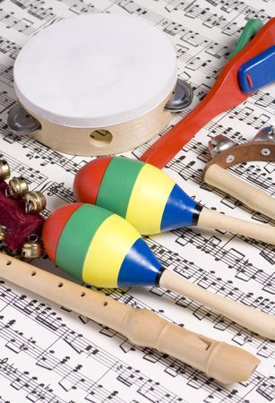 cymbals: Colorful childrens instruments laying on top of a complicated musical score