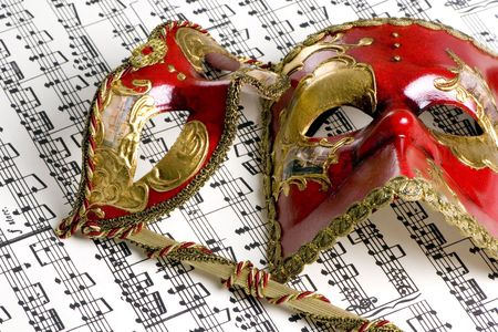 Two venetian masks lay on top of an old score of music photo