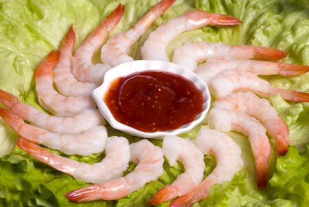 A circle of shrimp cocktail on a lettuce bed photo