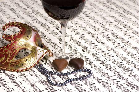 letras musicales: Un vaso de vino tinto negro con un collar de perlas y dos chocolates. Compartir el vino con un amante desconocido  Foto de archivo
