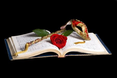 An old music book lays open with a mask and a single red rose on top. photo