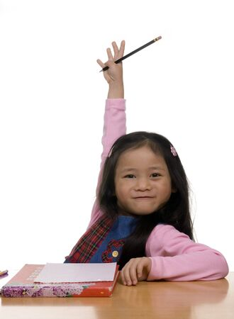 A young girl holds her hand in the air.... I know...pick me pick me. Stock Photo