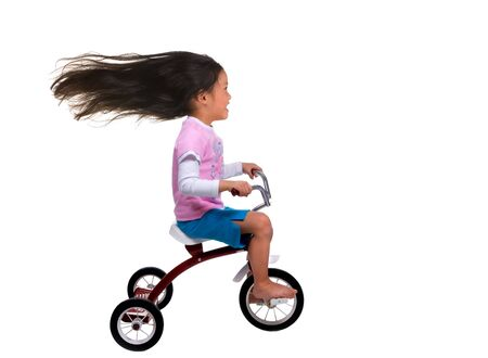 tricycle: A young girl is cruising on her tricycle.... speed demon