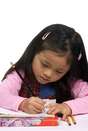A young Asian girl concentrates on writing a letter