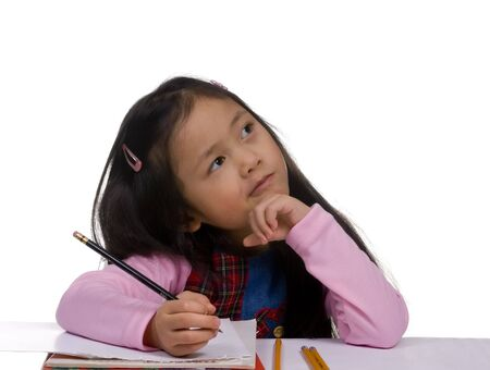 concentrating: A young girl is concentrating of what to write next. Early childhood, school, kindergarten.