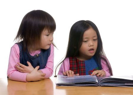 reading and writing: Two sisters share a book together. reading, writing, education, literacy Stock Photo