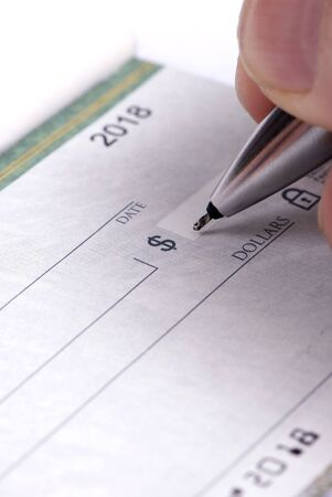 A person fills out a checkbook ...paying the bills photo