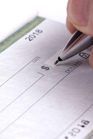 checkbook: Una persona llena una chequera ... el pago de las facturas  Foto de archivo