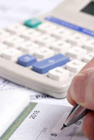 A person fills out a check... paying the bills. photo