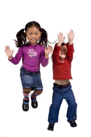 persona saltando: Dos hermanas que saltan y que juegan. Playtime del tiempo de la diversi�n