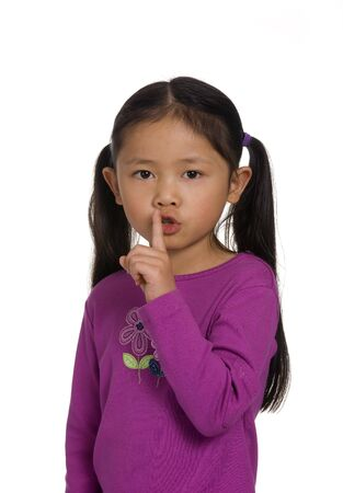 quite: A young girl hold her finger up.... shhhhhhhhhhh... quite. Stock Photo