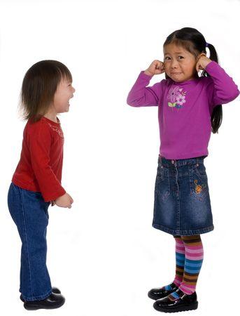 playmates: Dos hermanas est�n argumentando. Hermanita es dejar ir y hermana mayor, parece que est� a punto de llorar.  Foto de archivo