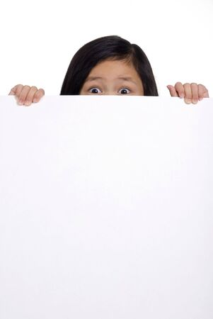 hold up: A young girl hold up a blank board and peeks over the top.