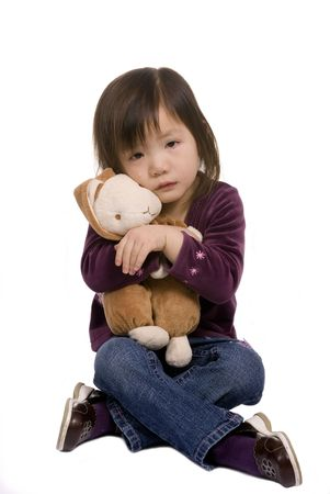 A young girl hugs here bunny as she cries. Stock Photo