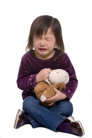 A young girl is upset and crying with her bunny in her lap photo