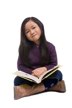A young girl enjoys reading a book Imagens