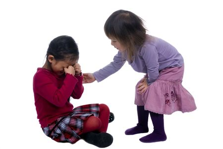 human kind: Younger sister offers comfort to her big sister after a fall.