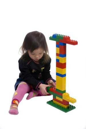 A young girl constructs a tower with building blocks. Isolated on white.