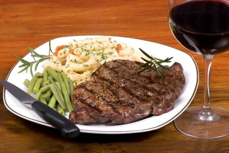 A rib eye steak with vegetables and past with red wine