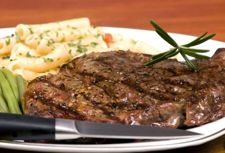 rib eye: A rib Eye steak with pasta and vegetables