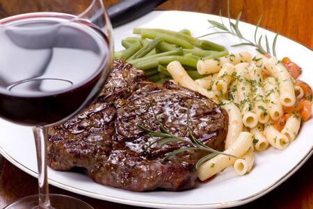 rib eye: A grilled rib eye steak with vegetables, pasta and red wine