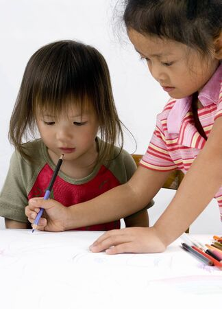 Two sisters draw a picture together. Sharing, siblings, help, teaching Stock Photo - 792741