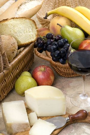 chees: An assortment of breads with a glass of red wine and fruit with chees and fruit. Stock Photo