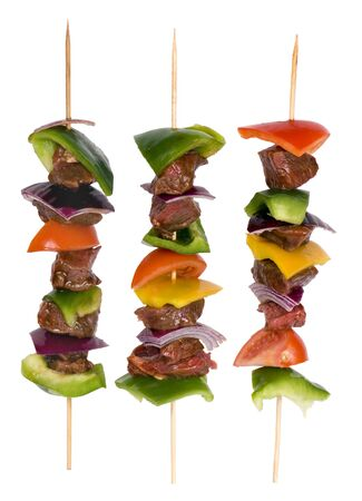 shish: Preparing fresh beef steak shishkabobs with vegatables ready for the grill. Isolated on white