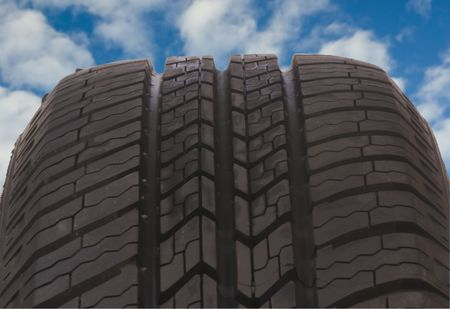 radial tire: A close macro shot of an all season radial tire... cruising with blue skies.