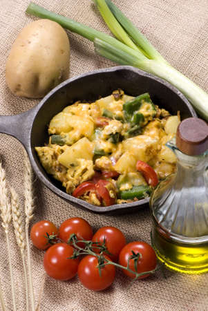A hearty start to your day with a breakfast skillet of potatoes, eggs, fresh vegetables with melted cheese on top. Stock Photo - 821042