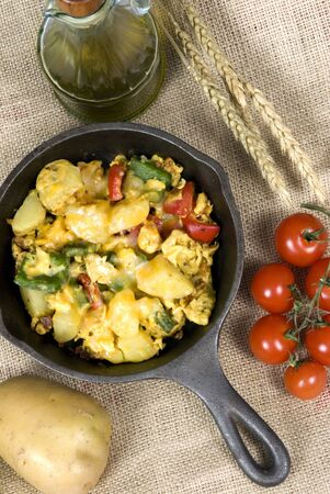A hearty start to your day with a breakfast skillet of potatoes, eggs, fresh vegetables with melted cheese on top. Stock Photo - 821043
