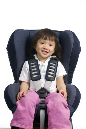 A young girl is straped into a car seat. Safety and security. isolated on white