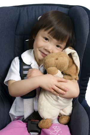 strapped: A young girl strapped into a car seat hold her bunny to keep it safe. Stock Photo