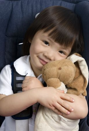 strapped: A young girl is strapped into a car seat for safety and holds her bunny. Stock Photo