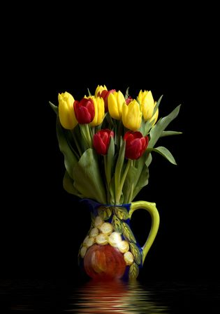 A pitcher full of red and yellow tulips with heavy shadows reflecting in water photo