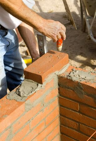 cement pile: A brick layer levels his bricks as he builds a wall Stock Photo