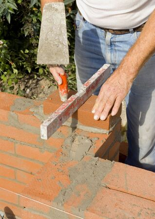 A brick layer taps on the bricks to put them in place.