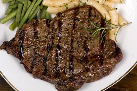 A juicy ribeye steak with pasta and fresh vegteables awaits you....