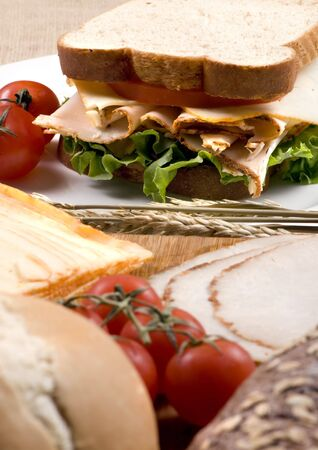A fresh deli sandwich with tomatoes cheese, lettuce and lots of turkey meat. Stock Photo