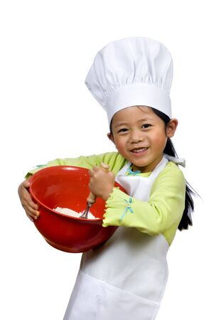 A young girl having fun in the kitchen making a mess....I mean making cookies. Education, learning, cooking, childhood Stock Photo