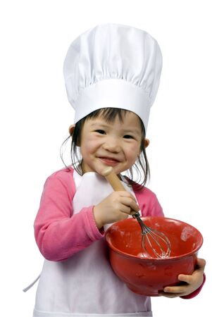 asian cook: A young girl having fun in the kitchen making a mess....I mean making cookies. Education, learning, cooking, childhood Stock Photo