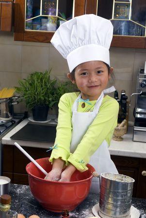 children cooking: Dos hermanas j�venes tienen diversi�n en la cocina que hace un medio del l�o....I que hace las galletas. Educaci�n, aprendiendo, cocinando, ni�ez