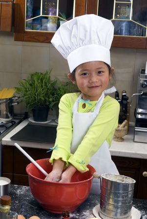 children cooking: Two young sisters have fun in the kitchen making a mess....I mean making cookies. Education, learning, cooking, childhood